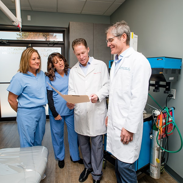 Our Advanced EndoCare specialists reviewing a patient's file while standing next to a machine