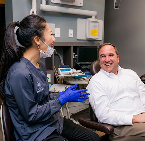 Our endodontist talking to a male patient as he sits in the chair