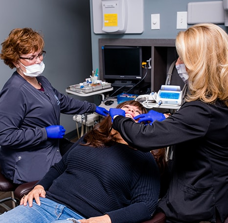 Our specialist and a dental assistant performing surgery on a woman who is sedated