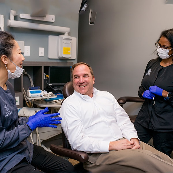 An older man sitting in the dentist's chair while smiling alongside two of our team