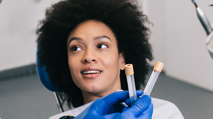A woman sitting in the dentist's chair and the doctor holding two test tubes