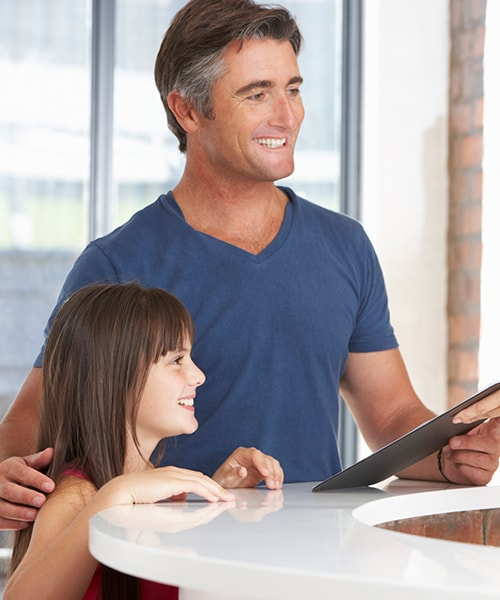 A man with his daughter receiving a notepad after he has been referred to our endodontist in Fishers, IN