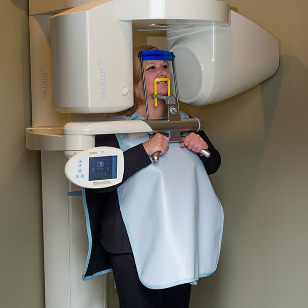 A woman at a dentist scanner standing and smiling