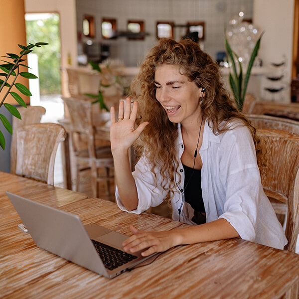 A young woman sitting at her desk while doing an virtual consultation with her laptop
