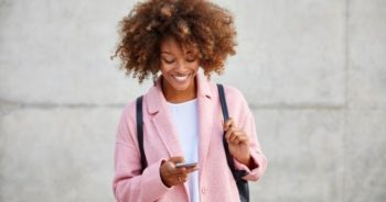 A patient in a pink jacket, white top, and black backpack talking to a dentist online on her phone